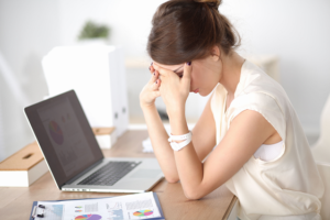 a stressed woman using a laptop