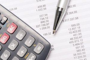 a calculator laying on a finance balance sheet