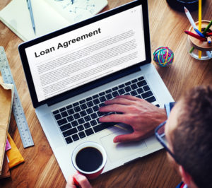 a man looking at a loan agreement online