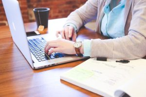 a woman using a laptop on a desk