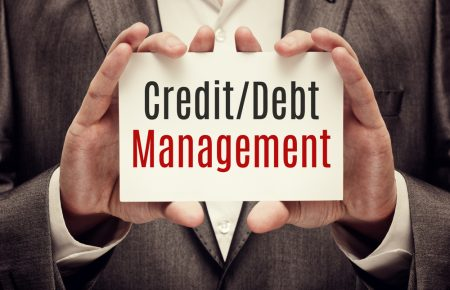 Credit/Debt management sign held by a person in both hands.