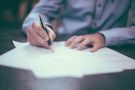 Man signing a PPI claim form.
