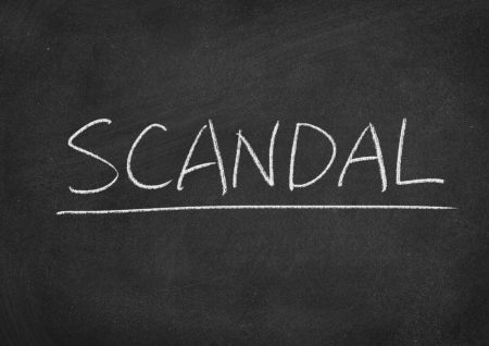"The word ""SCANDAL"" written on a chalkboard."