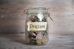 Coins in glass money jar with pension label, mis-sold pension claims management software concept
