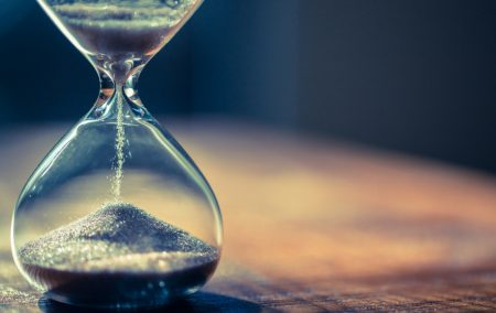 Sand running through the bulbs of an hourglass measuring the passing time in a countdown to PPI claims deadline
