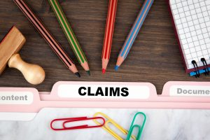 "a folder labeled ""claims"" on top of table with pencils and paper clips"