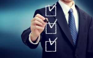 Businessman ticking off a checklist on the key features of the best claims management software.