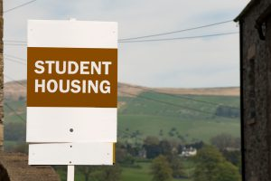 Orange and white student housing sign used for landlords' property management.