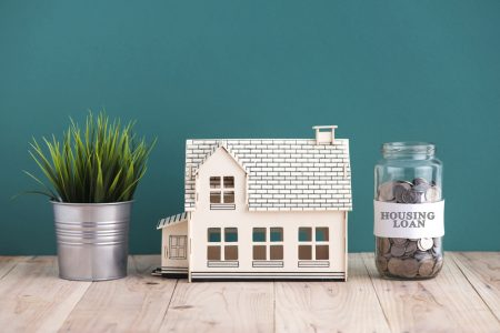 "Mortgage miscalculation claims concept with miniature house and jar of coins labeled as ""housing loans""."