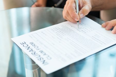 Person's hand signing an insurance claim form.