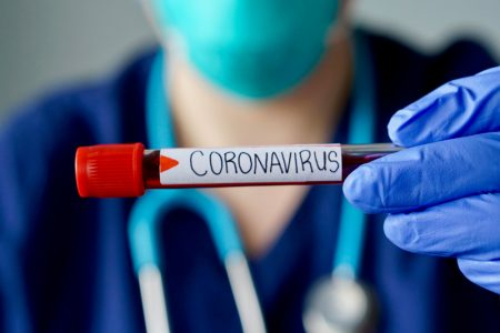 Nurse wearing respirator mask holding a positive blood test result for Coronavirus.